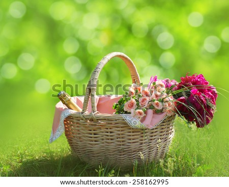 Romance, love and valentine's day concept - wicker basket with bouquet of flowers, bottle wine on the grass. Spring fresh sunny background