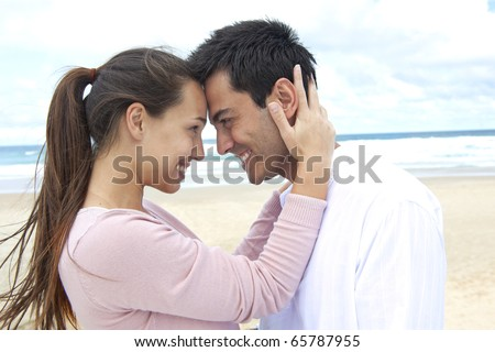 romance on vacation: couple in love on the beach flirting - stock photo