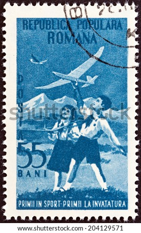ROMANIA - CIRCA 1953: A stamp printed in Romania issued for the 4th anniversary of Romanian Pioneers Organization shows boy and girl flying model gliders, circa 1953.