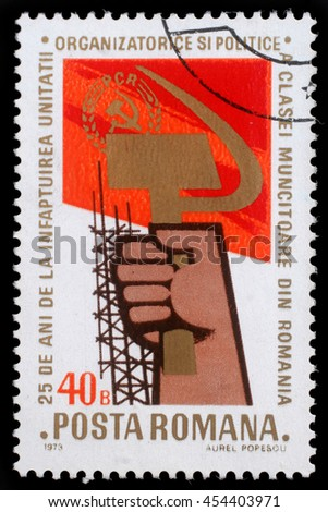 ROMANIA - CIRCA 1973: A stamp printed in Romania showing a hand holding sickle and hammer, circa 1973 - stock photo