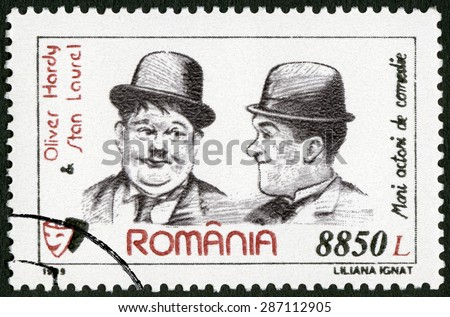 ROMANIA - CIRCA 1999: A stamp printed in Romania shows Oliver Hardy (1892-1957) and Stan Laurel (1890-1965), series Comic Actors, circa 1999 - stock photo
