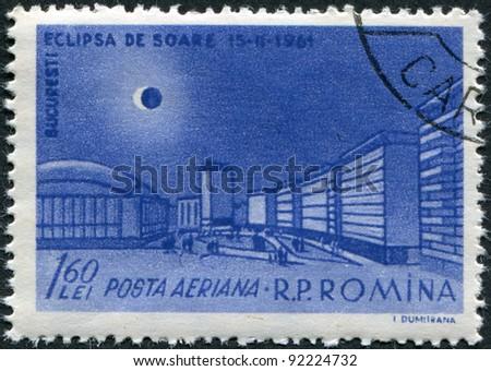 ROMANIA - CIRCA 1961: A stamp printed in the Romania, shows the Republic Square in Bucharest and the solar eclipse, circa 1961 - stock photo