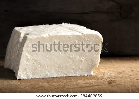 "Romanian cheese called ""telemea"" on table on wooden background"