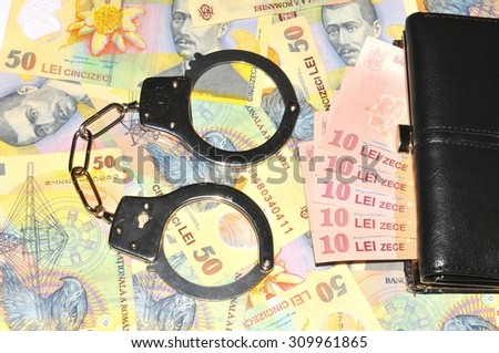 Romanian currency (lei) background and handcuffs  - stock photo