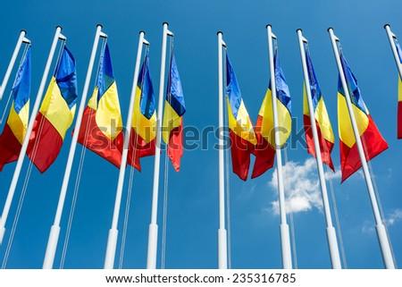 Romanian Flag Poles On Blue Sky - stock photo