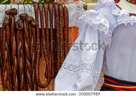 Romanian traditional sausages hanging on a fence, in a setting with specific costumes from Maramures, Romania. - stock photo