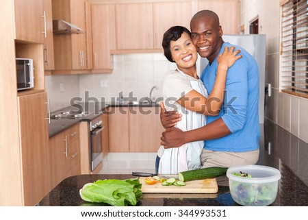 romantic african american couple embracing in kitchen  - stock photo