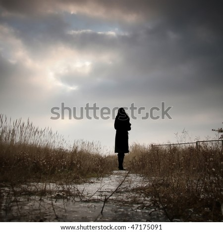 Romantic and nostalgic photograph of a girl silhouette staring at the winter sky - stock photo