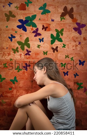 Romantic and nostalgic teenage girl sitting on the floor with colorful butterflies on a brick wall - stock photo