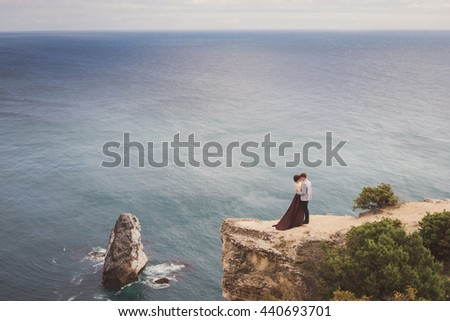 Romantic and stylish caucasian couple standing on the background of spectacular sea view. Love, relationships, romance, happiness concept.