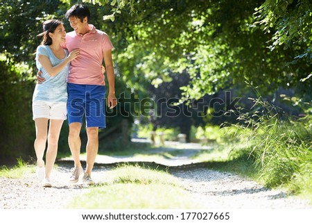 Romantic Asian Couple On Walk In Countryside - stock photo