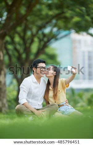 Romantic Asian couple taking selfie in the park