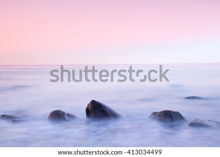 Romantic atmosphere in peaceful morning at sea. Big boulders sticking out from smooth wavy sea. Pink horizon with first hot sun rays. - stock photo