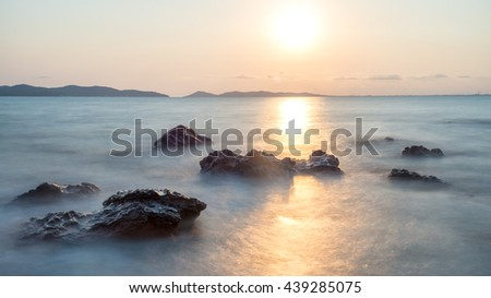 Romantic atmosphere in peaceful sunset at sea. Big boulders sticking out from smooth wavy sea. - stock photo