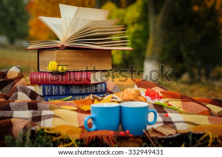 Romantic autumn still life with books, plaid, croissant, coffee cups and leaves - stock photo