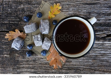 Romantic autumn still life with cookies, cup of tea, blackthorn berries and leaves at wooden board, top view - stock photo
