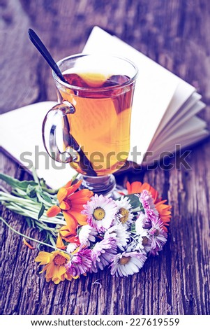 romantic autumn vintage background with books and tea/ cup of herbal tea on wooden background