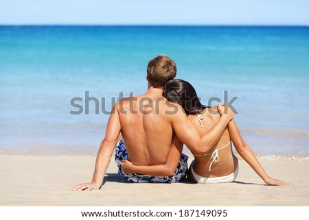 Romantic beach couple in love relaxing on vacation enjoying ocean view together sitting in the sand embracing and hugging. Beautiful young multiracial couple, Asian woman, Caucasian man. - stock photo