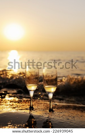 Romantic beach evening on the sunset with two glasses of white wine - stock photo