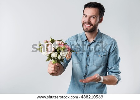Romantic bearded man smiling and holding a bunch of flowers.