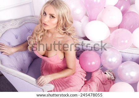 Romantic beautiful blonde woman in pink dress posing over balloons, looking at camera. - stock photo