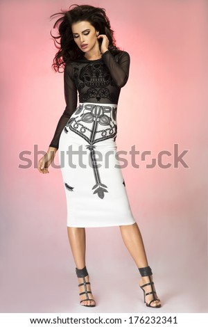 Romantic beautiful brunette woman posing in studio wearing fashionable dress, looking away. - stock photo