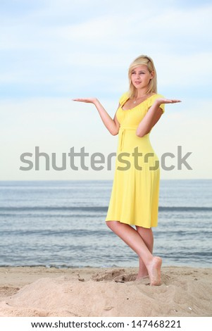 Romantic Beautiful smiling girl in the yellow dress water beach