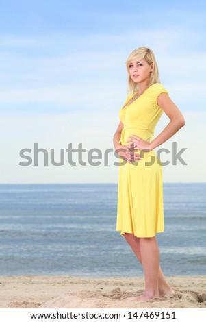 Romantic Beautiful smiling girl in the yellow dress water beach - stock photo