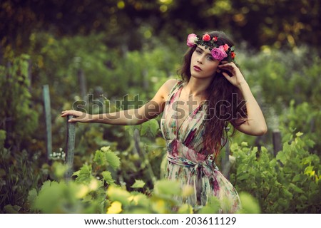 romantic beautiful woman summer portrait with wreath of flowers in vineyard - stock photo