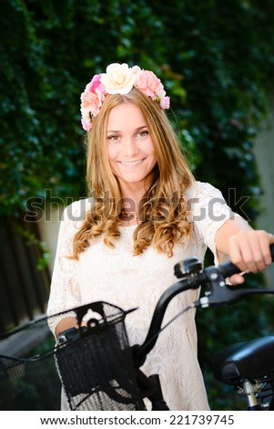 romantic beautiful young blonde woman riding bicycle in summertime - stock photo
