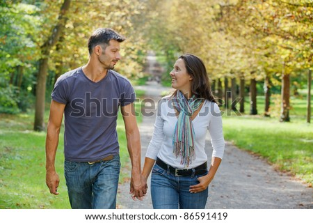 Romantic  Beautiful young couple walking in autumn park - stock photo