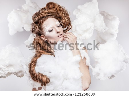 Romantic beauty with magnificent hair wandering in clouds. Studio fashion portrait.