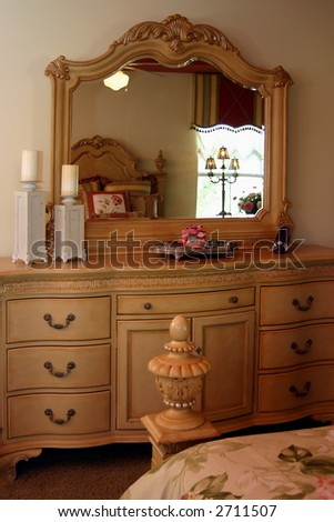 romantic bedroom with bed reflected in mirror on dresser - stock photo