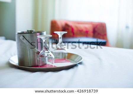 Romantic bedroom with wine glasses and ice bucket in luxury hotel interior