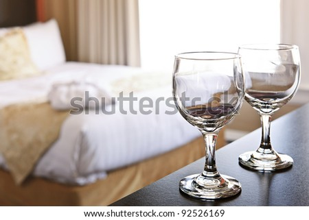 Romantic bedroom with wine glasses in luxury hotel interior - stock photo