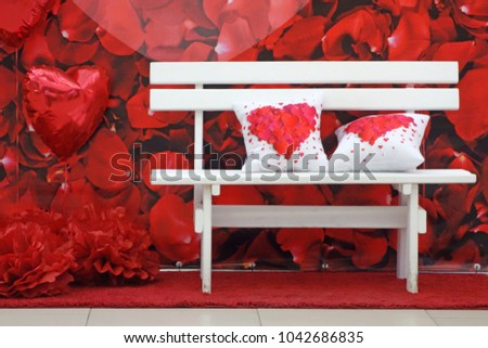 Romantic bench for lovers and two cushions with hearts of red petals