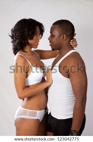 Romantic black couple in the heat of passion, she is tearing his shirt off while he is leaning forward for a kiss - stock photo