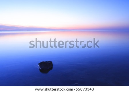 Romantic blue sunset at sea with a rock in the water - stock photo