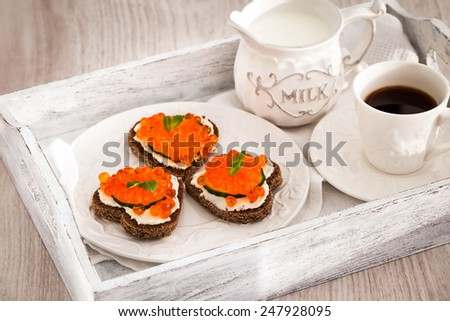 Romantic breakfast with heart shaped toasts  with red caviar and coffee - Valentine concept - stock photo
