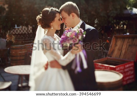 Romantic bride & groom hugging in vintage french cafe - stock photo