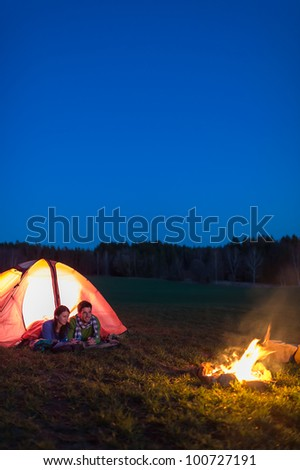 Romantic camping night couple lying in front tent by campfire - stock photo
