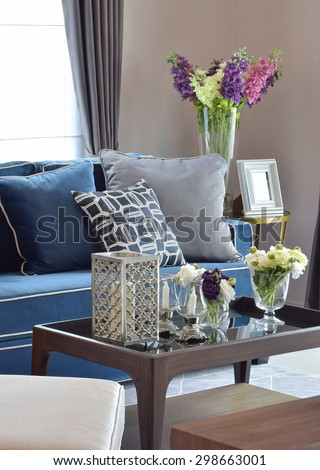 Romantic candle set with beige and blue modern classic sofa in warm living room - stock photo