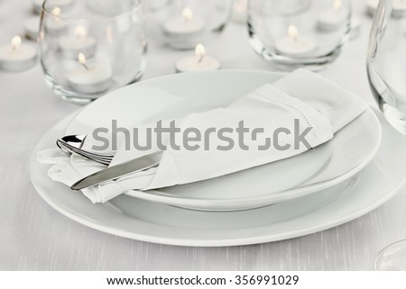 Romantic candlelight table setting. Shallow depth of field with selective focus on rose. - stock photo