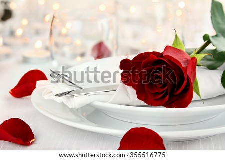 Romantic candlelite table setting with long stem red rose. Shallow depth of field with selective focus on rose. - stock photo