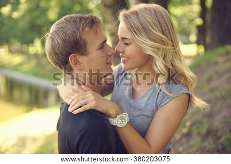 Romantic caucasian  couple hugging in park. Young beautiful blonde girl looking at her boyfriend  - stock photo