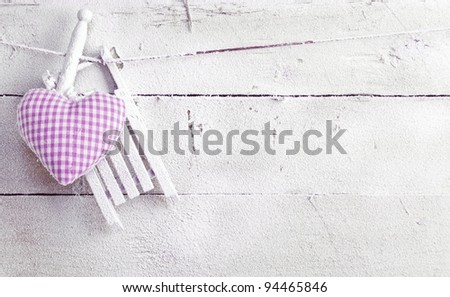 Romantic checked violet needlework heart for Valentines hanging on old painted white boards with copyspace - stock photo