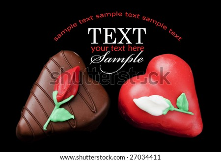 Romantic chocolate and red heart shaped petits fours (small cakes) on a field of black with sample text - stock photo