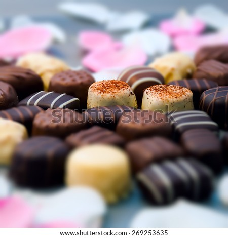 Romantic chocolate truffles and white roses heart shape setup square composition - stock photo