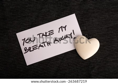 Romantic concept of attraction and love for a sweetheart with the handwritten message - You Take My Breath Away - on a card with a white heart on a textured black background. - stock photo
