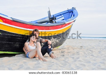 Romantic couple and boat on the beach - stock photo
